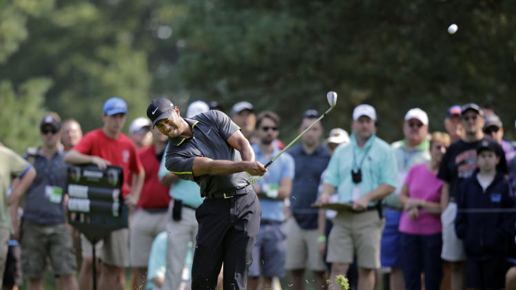 Tiger Woods hits his approach shot to the 11th green during the second round of the Bridgestone Invitational golf tournament Friday, Aug. 1, 2014, at Firestone Country Club in Akron, Ohio. (AP Photo/Mark Duncan)