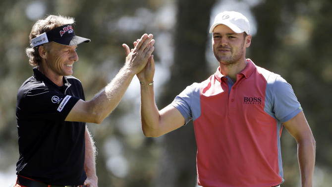 Martin Kaymer, right, of Germany, high fives Bernhard Langer, of Germany, after teeing off on the first hole of the par three competition before the Masters golf tournament Wednesday, April 10, 2013, in Augusta, Ga.  (AP Photo/Darron Cummings)