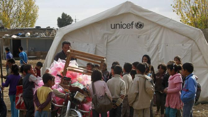 Syrian refugee children gather around a street vendor at a Syrian refugee camp in the Bekaa Valley