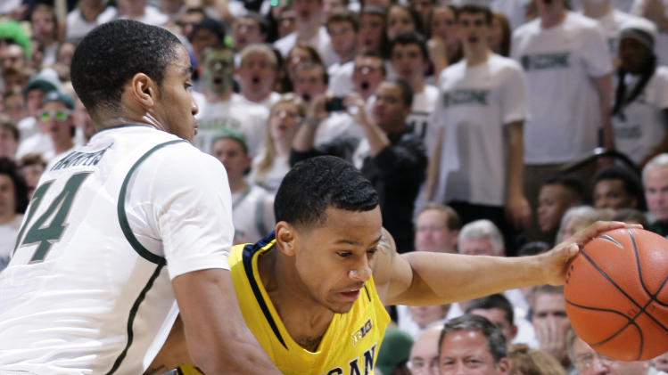 Michigan's Trey Burke, right, is fouled by Michigan State's Gary Harris (14) as he drives during the first half of an NCAA college basketball game, Tuesday, Feb. 12, 2013, in East Lansing, Mich. (AP Photo/Al Goldis)