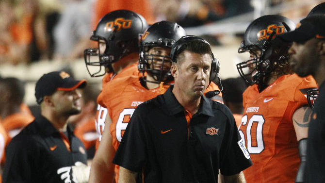 Oklahoma State coach Mike Gundy walks along the sidelines during the fourth quarter of an NCAA college football game against Texas in Stillwater, Okla., Saturday, Sept. 29, 2012. Texas won 41-36. (AP Photo/Sue Ogrocki)