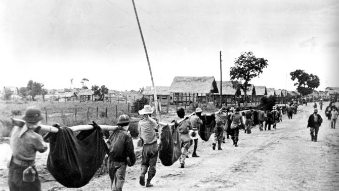 FILE - A photo released by the U.S. military in 1945, after it was captured from the Japanese, shows allied prisoners of war in the Philippines carrying their comrades in slings. In 2009, John E. Love, a Bataan Death March survivor , joined a campaign with other Bataan Death March survivors to change the caption of this photo, one of the most famous photos in AP's library about the march. The photo, thought to be of the Bataan Death March, actually was an Allied POW burial detail. Following a six-month investigation, The AP corrected the caption in 2010, 65 years after the image was first published. AP archivists confirmed Love's account of the burial detail at a prisoner-of-war camp in the weeks that followed the Death March. Love died Monday, March 17, 2014 after a long battle with cancer. He was 91. (AP Photo/U.S. Marine Corps)