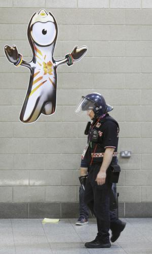 A security officer walks past a poster of the Olympic mascot Wenlock in the ExCel Center before the start of the 2012 Summer Olympics, Thursday, July 26, 2012, in London. (AP Photo/Charlie Neibergall)