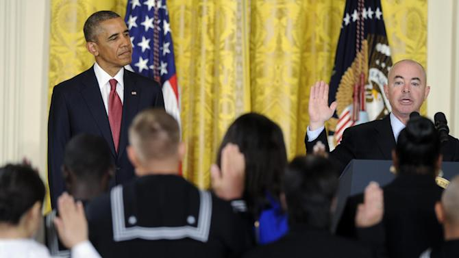 President Barack Obama watches at left as Deputy Homeland Security Secretary Alejandro Mayorkas administers the oath of allegiance during a naturalization ceremony for active duty service members and civilians, Friday, July 4, 2014, in the East Room of the White House in Washington. Obama highlighted a positive side of the immigration debate by presiding over an Independence Day citizenship ceremony for service members who signed up to defend the U.S. even though they weren't American citizens. (AP Photo/Susan Walsh)