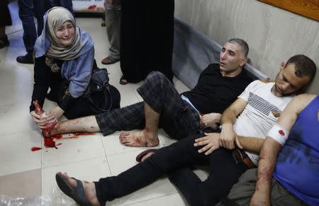 Palestinian woman cries as she tries to stop the bleeding of her brother's foot at a hospital in Gaza City