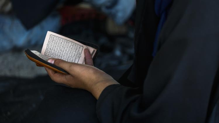 A suspected Uighur from China's region of Xinjiang, reads the Koran inside a temporary shelter after being detained near the Thailand-Malaysia border in Hat Yai