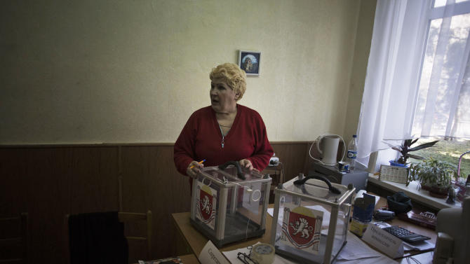 A Ukrainian woman, who is a member of the district electoral committee, holds a ballot box during preparations for Sunday's referendum at a polling station in Simferopol, Ukraine, Saturday, March 15, 2014. Tensions are high in the Black Sea peninsula of Crimea, where a referendum is to be held Sunday on whether to split off from Ukraine and seek annexation by Russia. (AP Photo/Manu Brabo)