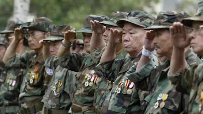 FILE - In this Dec. 21, 2005 file photo, a group of Lao and Hmong veteran soldiers who fought in Vietnam and Loas salute during a ceremony to dedicate a new Lao Hmong American War Memorial at Courthouse Park in downtown Fresno, Calif. A former leader of the CIA-backed ethnic Hmong guerrilla army in Laos that assisted the U.S. military in fighting against communists during the Vietnam War has been deported to his homeland from Thailand, Thai officials and minority rights advocates said Wednesday, July 2, 2014. Moua Toua Ter and fellow Hmong led a desperate existence on the run in the jungles of Laos for more than two decades. He had been sheltering in Thailand for eight years while seeking resettlement in a third country. More than 300,000 refugees from Laos, mostly Hmong, fled after the communist takeover, with many resettling in the United States. (AP Photo/The Fresno Bee, Craig Kohrluss, File)
