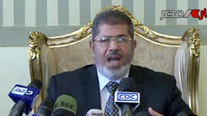 This image made from video broadcast on Egyptian State Television shows President Mohammed Morsi making a statement as he appears with members of the Egyptian security forces, unseen, after their release by kidnappers, in Cairo, Egypt, Wednesday, May 22, 2013. Six Egyptian policemen and a border guard kidnapped by suspected militants in the volatile Sinai Peninsula last week were freed by their captors Wednesday after successful mediation, the country's military spokesman said. (AP Photo/Egyptian State Television) EGYPT OUT