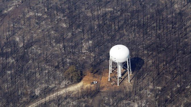 FILE - In this Sept. 7, 2011 file photo, n area destroyed by wildfire surrounds a water tower, Wednesday, Sept. 7, 2011, in Bastrop, Texas. The fire has destroyed more than 600 homes and blackened about 45 square miles in and around Bastrop. As the soggy Northeast tries to dry out from flooding and Texas prays for rain that doesn't come, it seems like an ideal match of oversupply and unquenchable demand. It isn't.  (AP Photo/Eric Gay, File)