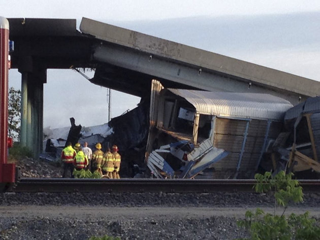 Emergency personnel looking at an overpass that collapsed after two freight trains collided at a rail intersection in Missouri are pictured in this photo courtesy of KFVS12