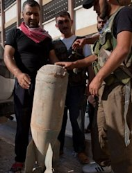 Free Syrian Army members precariously handle an unexploded bomb that was dropped by a Syrian Army MIG fighter jet onto a hospital in the Sahoul area of Aleppo, near the headquarters of the opposition on August 7. Syria said its troops seized a rebel-held Aleppo district on Wednesday after storming it and &quot;annihilating&quot; most of the insurgents
