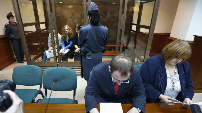Feminist punk group Pussy Riot members, from left, Maria Alekhina, Yekaterina Samutsevich and Nadezhda Tolokonnikova sit in a glass cage at a court room in in Moscow, Wednesday Oct. 10, 2012. Lawyers Violetta Volkova, right, and Lev Lyalin, foreground center, defending members of feminist punk group Pussy Riot, sit in front.(AP Photo/Sergey Ponomarev)