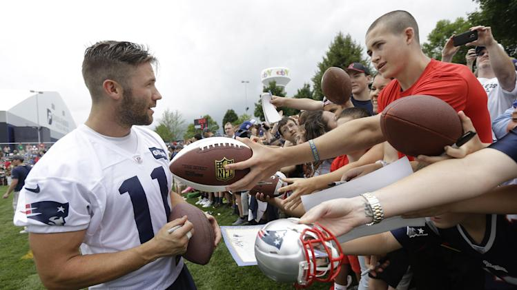 New England Patriots wide receiver Julian Edelman, left, signs autographs following an NFL football training camp practice at Gillette Stadium, Thursday, July 24, 2014, in Foxborough, Mass. (AP Photo)