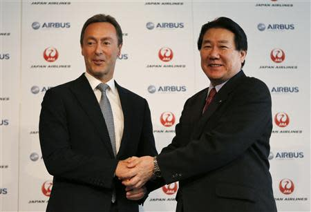 Japan Airlines President Yoshiharu Ueki shakes hand s with Airbus Chief Executive Fabrice Bregier during their joint news conference in Tokyo