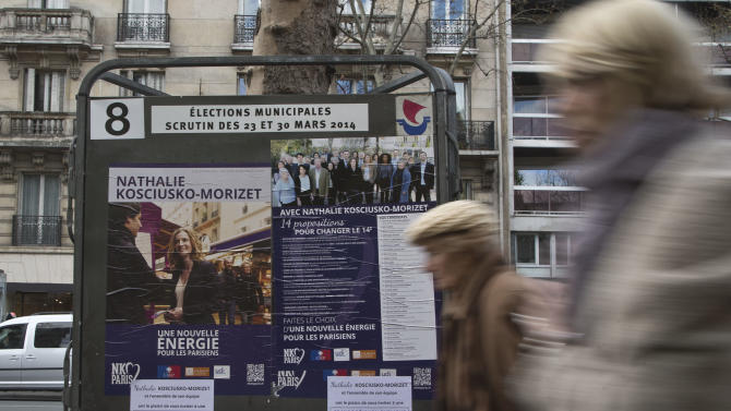 Women walk past of a campaign poster for the upcoming municipal elections of the conservative UMP party candidate Nathalie Kosciusko-Morizet, in Paris, Friday, March 21, 2014. Two women are at war to be the new face of Paris, the first time in this city's long history that the mayor won't be a man. Municipal elections will take place on March 23 and 30 throughout France. (AP Photo/Michel Euler)