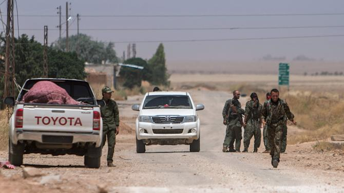 YPG fighters gather along a road in the town of al-Mabroukah