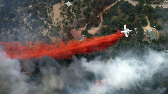 An aircraft lays down a line of fire retardant between a wildfire and homes in the dry, densely wooded Black Forest area northeast of Colorado Springs, Colo., Thursday, June 13, 2013. More than 350 homes have been lost in what is now the most destructive wildfire in Colorado history, surpassing last year's Waldo Canyon fire, which burned 347 homes, killed two people and led to $353 million in insurance claims. (AP Photo/John Wark)
