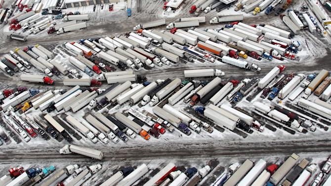 In this aerial photo taken on March 3, 2014, semitrailers fill up a truck stops in West Memphis, Ark. Some motorists on the highway in eastern Arkansas were stranded overnight due to lingering icy conditions from a weekend winter storm. An Arkansas highway department spokesman said Tuesday that traffic can't get moving consistently because of repeated accidents. (AP Photo/The Commercial Appeal, Mike Brown)