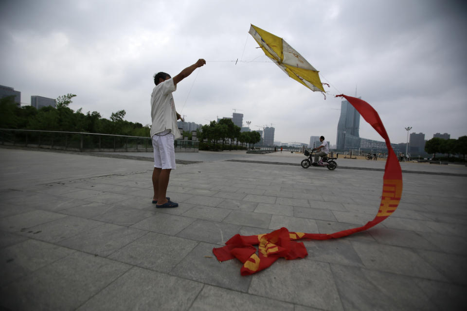 A man flies a kite at a park near the Hefei City Intermediate People's Court Wednesday, Aug. 8, 2012  in Hefei, Anhui Province, China. The murder trial of Gu Kailai, wife of ousted Chinese politician Bo Xilai, will start Thursday at the court. (AP Photo/Eugene Hoshiko)