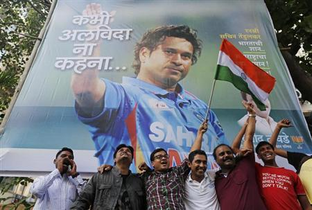 Cricket fans holding an Indian national flag shout slogans in front of a billboard of cricketer Sachin Tendulkar outside a stadium in Mumbai November 14, 2013. REUTERS/Danish Siddiqui
