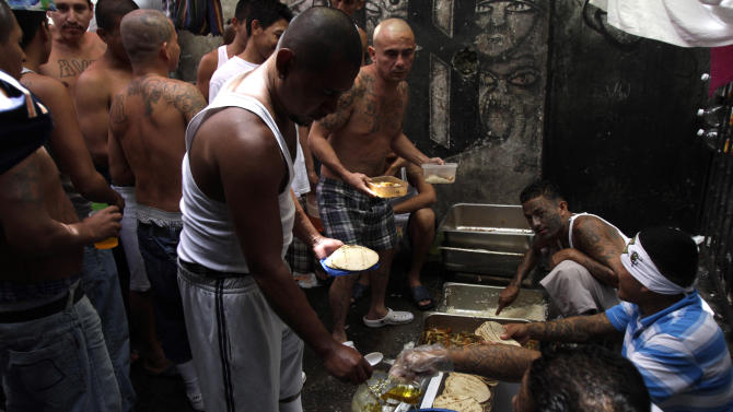 In this Sept. 1, 2012 photo, inmates belonging to the Mara 18 gang serve a meal for fellow gang members inside the prison in Cojutepeque , El Salvador.  Six months after El Salvador brokered an historic truce between two rival gangs to curb the nation's daunting homicide rate, officials are split over whether the truce actually works. The gangs, which also operate in Guatemala and Honduras, are seeking truce talks in those countries as well.(AP Photo/Luis Romero)