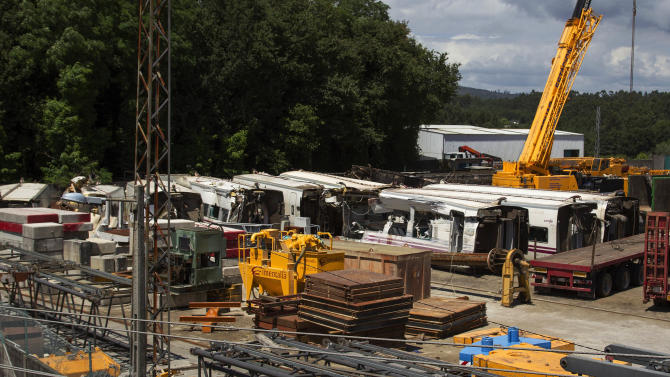 """Wrecked carriages sit at a train depot in Padron, near Santiago de Compostela, Spain, Friday July 26, 2013 after they were taken there from the scene of a train accident. Investigators have taken possession of the """"black boxes"""" of the Spanish train that hurtled at high-speed along a curve and derailed, killing 80 people, a court official said Friday. Analysis will be performed to determine why the train was traveling far above the speed limit when it crashed near a station in Santiago de Compostela, in the northwestern Galicia region, said court spokeswoman Maria Pardo Rios. The train's operator remained hospitalised Friday and will be questioned by police but she said the interview will not happen Friday. (AP Photo/Lalo R. Villar)"""