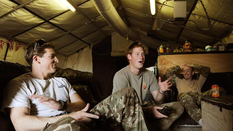 In this photo taken Nov. 3, 2012, and made available Monday Jan. 21, 2013 of Britain's Prince Harry, center, or just plain Captain Wales as he is known in the British Army, reacts as he plays computer games with his fellow Apache Helicopter crew, during his 12 hour VHR (very high ready-ness) shift at the British controlled flight-line in Camp Bastion southern Afghanistan. The Ministry of Defense announced Monday that the 28-year-old prince is returning from a 20-week deployment in Afghanistan, where he served as an Apache helicopter pilot with the Army Air Corps.  (AP Photo/ John Stillwell, Pool)