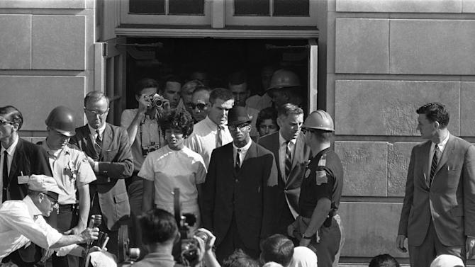 "FILE - In this June 11, 1963 file photo, Vivian Malone and James Hood stand in the doorway of Foster Auditorium where they hold what they called their ""first and final news conference"" after the two African-American students registered at the University of Alabama at Tuscaloosa, Ala. Earlier, Gov. George Wallace had barred their way from the same doorway. Hood, one of the first black students at the University of Alabama, has died. He was 70. Officials at Adams-Buggs Funeral Home in Gadsden said they are handling arrangements for Hood, who died Thursday, Jan. 17, 2013. Details concerning Hood's funeral are not complete, funeral home officials said. (AP Photo/File)"