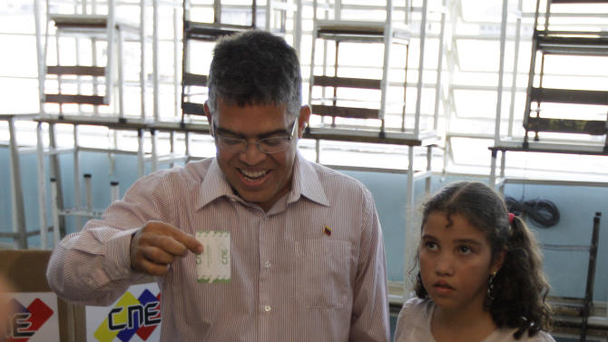 Elias Jaua, left, Venezuela's former Vice President and candidate for governor of Miranda state, accompanied by his daughter Natalia, casts his ballot at a polling station in Caracas, Venezuela, Sunday, Dec. 16, 2012. Venezuelans are choosing governors and state lawmakers in elections that have become a key test of whether President Hugo Chavez's movement can endure if the leader leaves the political stage. (AP Photo/Ariana Cubillos)