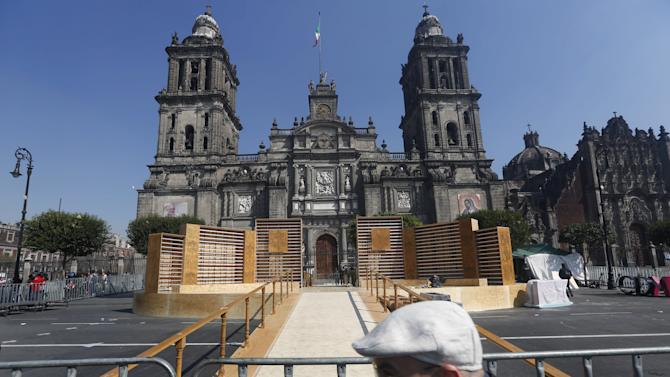A man passes in front of a stage in preparation for the upcoming visit of Pope Francis outside Metropolitan Cathedral in Mexico City