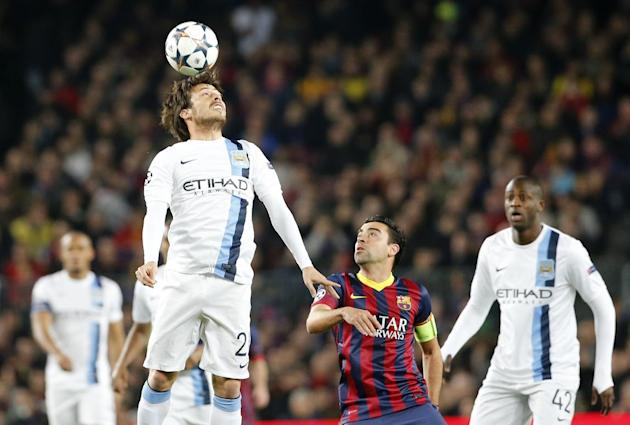 Manchester City's David Silva, 2nd left out jumps FC Barcelona's Xavi Hernandez during a Champions League, round of 16, second leg, soccer match between FC Barcelona and Manchester City at the