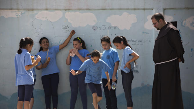 In this photo taken Tuesday, May 26, 2015, Arab Israeli Christian school children play at the Terra Santa School in the mixed Jewish-Arab city of Ramle, Israel. Private Christian schools are among Israel's highest ranked educational institutions, established by churches in the Holy Land hundreds of years ago long before Israel was established. But school administrators are accusing Israel of slashing their funding as a pressure tactic to get them join the Israeli public school system a move they say would interfere with the schools' Christian values and high academic achievements. (AP Photo/Oded Balilty)