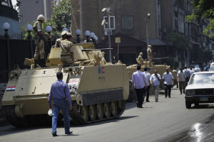 Egyptian military soldiers stand guard atop armored …