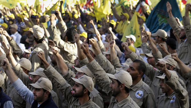 "Members of the demining unit of Hezbollah, raise up their hands as they shout slogans in support of pro-Hezbollah leader Sheik Hassan Nasrallah, during a rally commemorating ""Liberation Day,"" which marks the withdrawal of the Israeli army from southern Lebanon in 2000, in Mashghara village Bekaa valley, Lebanon, Saturday May 25, 2013. Nasrallah says his Shiite militant group will not stand idly by while its chief ally Syria is under attack. Nasrallah says Hezbollah members are fighting in Syria against Islamic extremists who pose a danger to Lebanon, publicly confirming for the first time that his men were fighting in Syria. (AP Photo/Hussein Malla)"