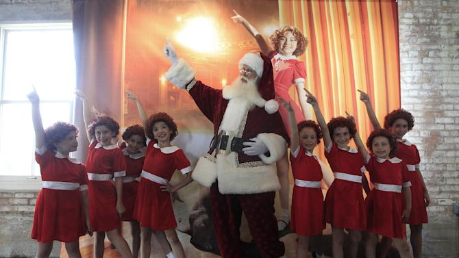With several Annies on hand, Brady White portrays Santa Clause, center, as he and the little actresses display the a gift Annie:The Musical Walk-on Role during the unveiling of the Neiman Marcus 2012 Christmas Book in Dallas, Tuesday, Oct. 9, 2012. For $30,000, the gift buys a walk on role in the Broadway musical.  (AP Photo/LM Otero)