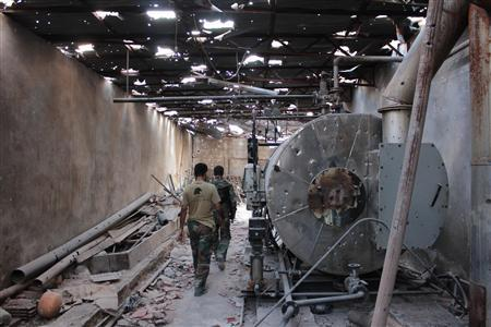 Free Syrian Army fighters walk with their weapons in a damaged factory in the al-Khalidiya neighbourhood of Aleppo