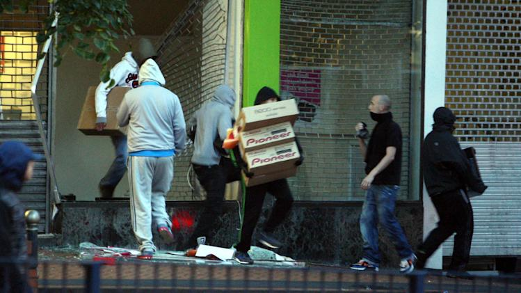 In this Tuesday Aug. 9, 2011 photo, youths run from an electronics store in Birmingham, England as disturbances saw looting and vehicles set alight. As Britain comes to grips with the causes of the past week's descent into anarchy, Prime Minister David Cameron has identified the growth of gangs as a key factor and is recruiting high-profile American anti-gang experts to help bring them to heel.   (AP Photo/David Jones/PA Wire)  UNITED KINGDOM OUT