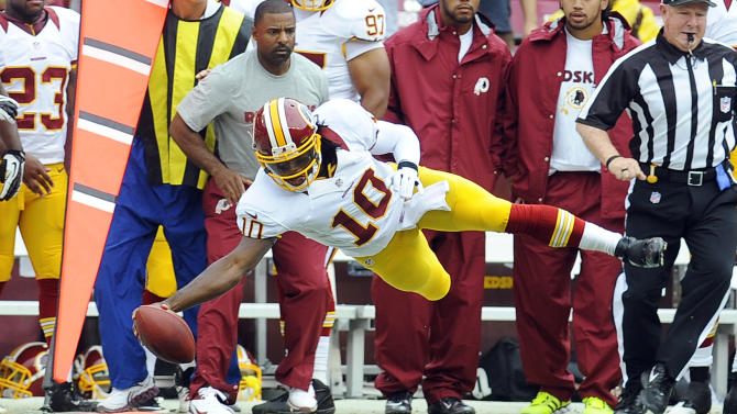 Washington Redskins quarterback Robert Griffin III dives for a first down during the first half of an NFL preseason football game against the Indianapolis Colts on Saturday, Aug. 25, 2012, in Landover, Md. (AP Photo/Richard Lipski)