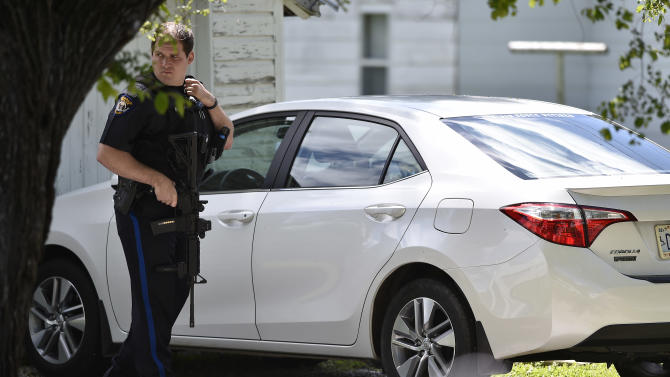 A Sedalia police officer was on alert Thursday, May 21, 2015, at a standoff in Sedalia, Mo.  where police believe they have a suspect in the slayings of Sandra Sutton and her teenage son Zachary Wade Sutton. Sandra Kay Sutton, who authorities said had been held captive in a wooden box for months before being freed about three weeks ago, was found dead early Thursday, along with her 17-year-old son, from what appear to be gunshot wounds, police said.  (Jill Toyoshiba/The Kansas City Star via AP)