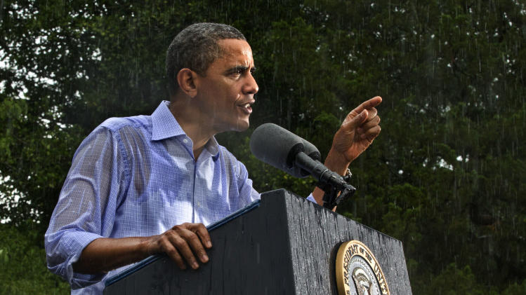 FILE - In this July 14, 2012 file photo, President Barack Obama campaigns for re-election in the heavy rain at Walkerton Tavern & Gardens in Glen Allen, Va., near Richmond.  It was a year of storms, of raging winds and rising waters, but also broader turbulence that strained our moorings. Our atmosphere, our politics, our economy — rarely in memory have they seemed in such constant agitation. (AP Photo/J. Scott Applewhite, File)