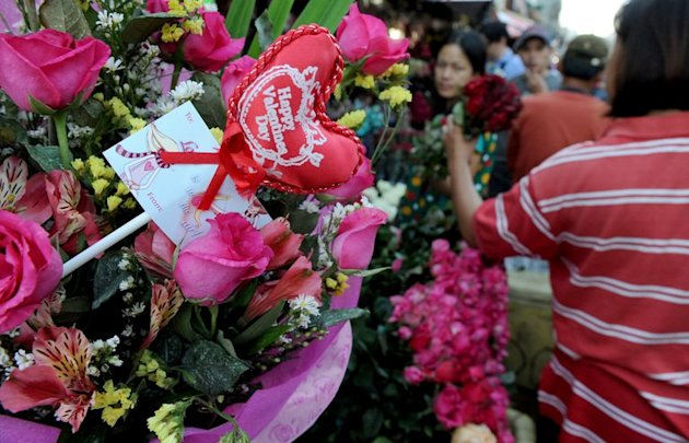 Flower shop owners buy wholesale flowers on the eve of Valentine's Day in Manila on February 13, 2013. Romantic Filipinos abroad have found a way to bridge the gap with loved ones at home on Valentine's Day -- via an online serenade service