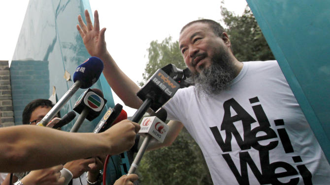 FILE - In this June 23, 2011 file photo, activist artist Ai Weiwei opens the gate to talk to journalists gathered outside his home in Beijing. Representatives of Ai's design firm entered a closed hearing Thursday, July 14, 2011 to challenge a US$1.85 million tax bill delivered by authorities after the dissident was released from nearly three months' detention. (AP Photo/Ng Han Guan, File)