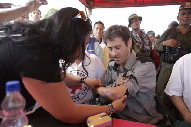 A woman checks a wound on the left arm of French journalist Romeo Langlois after his release by the FARC in San Isidro, Colombia, Wednesday, May 30, 2012. Langlois, who was wounded when he was taken b
