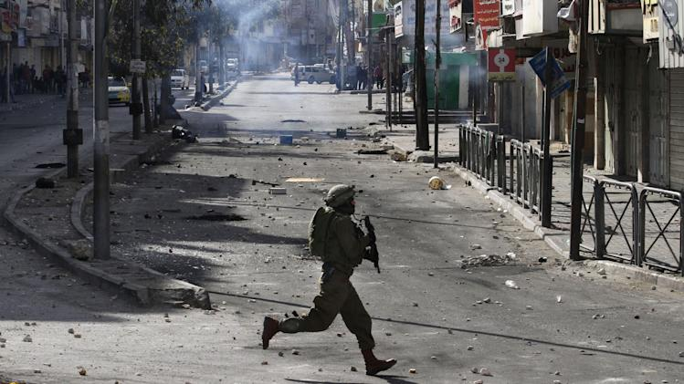 An Israeli soldier runs during riots with Palestinian protesters, not pictured, after the death of Maysara Abu Hamdiyeh in Israeli jail, in the West Bank city of Hebron, Wednesday, April 3, 2013. Palestinian prisoners have been rioting and hunger striking since a 64-year-old prisoner died of throat cancer on Tuesday. The Palestinians have blamed Israel for the man's death, saying he was not given proper medical care. The prisoner, Maysara Abu Hamdiyeh, had been serving a life sentence for his role in a foiled attempt to bomb a busy cafe in Jerusalem in 2002. (AP Photo/Nasser Shiyoukhi)