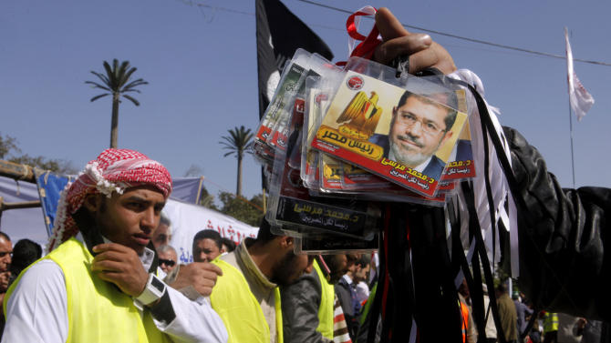 "An Egyptian vendor displays plastic cards with the picture of Islamist President Mohammed Morsi, during a rally outside Cairo University in Cairo, Egypt, Friday, Feb. 15, 2013. Around 5,000 mostly hardline Islamists are rallying in Egypt against a recent wave of protests that has killed around 70 people. Arabic reads ""Mohammed Morsi president of all Egyptians."" (AP Photo/Amr Nabil)"