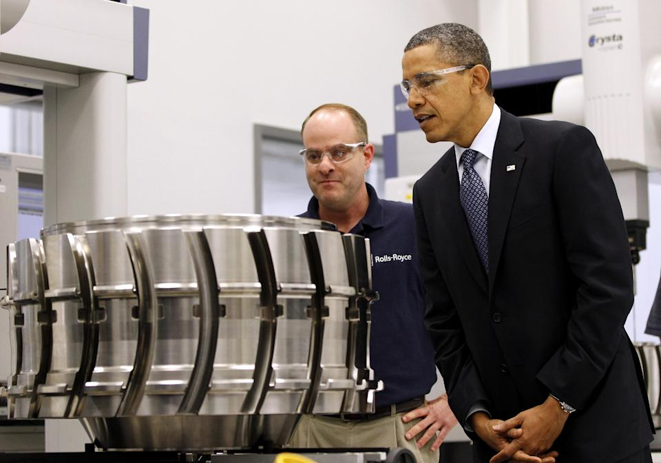 President Barack Obama looks at a aircraft component with employee Robert Abernathy during his tour of the Rolls-Royce Crosspointe jet engine disc manufacturing facility, Friday, March, 9, 2012, in Prince George, Va. (AP Photo/Pablo Martinez Monsivais)