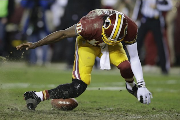 Washington Redskins quarterback Robert Griffin III twists his knees as he reaches for a loose ball after a low snap during the second half of an NFL wild card playoff football game against the Seattle