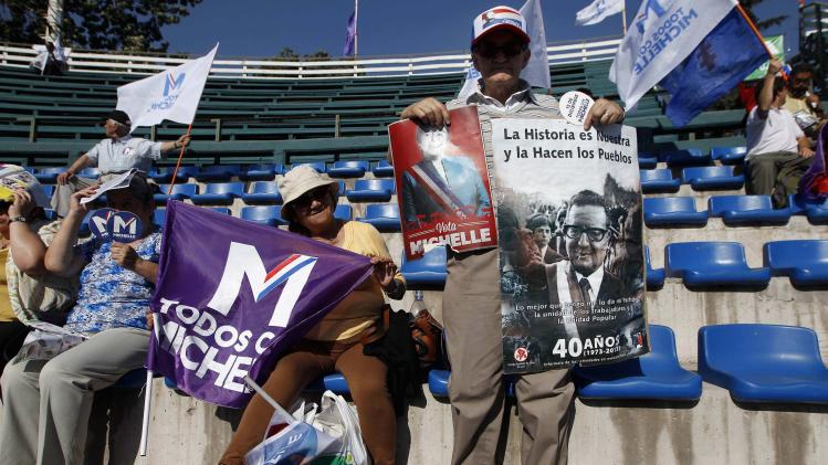A supporter of Chilean presidential candidate Bachelet holds poster of former Chilean President Allende during Bachelet's closing campaign rally in Santiago