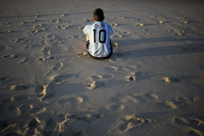 An Argentina soccer fan, wearing a Lionel Messi soccer jersey, sits on Copacabana beach the morning after his team was defeated by Germany at the Worl...